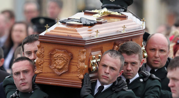 Police officers carry the coffin containing the remains of their colleague Police Constable Ronan Kerr to the church of the Immaculate Conception, in Beragh, Northern Ireland, on April 6, 2011. The funeral of a Northern Ireland policeman killed by a bomb planted by suspected dissidents took place on Wednesday with a remarkable show of cross-community unity. The First Minister of the British-controlled province, the Protestant Peter Robinson, broke with decades of tradition to attend his first ever Catholic mass as Constable Ronan Kerr was laid to rest. (photo: Peter Muhly/AFP/Getty Images)