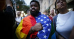 A man holds a flag during a vigil in solidarity for the victims killed at Pulse nightclub in Orlando.
