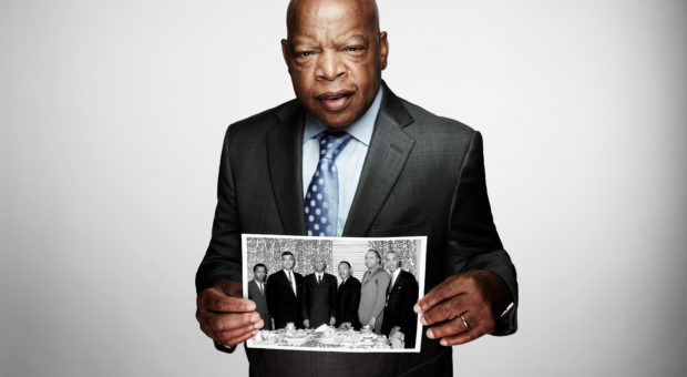John Lewis holds up a photo of a table of men.