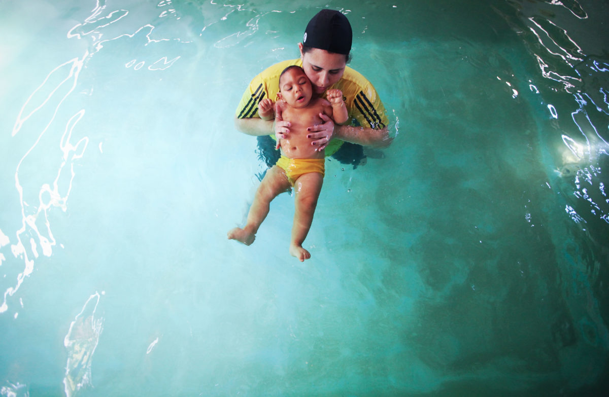 A child with microcephaly receives aquatic physiotherapy treatment with a doctor in Recife, Brazil.